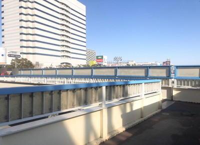 階段を上ると、歩道橋があります。歩道橋を行き止まりまで直進し、角を左折