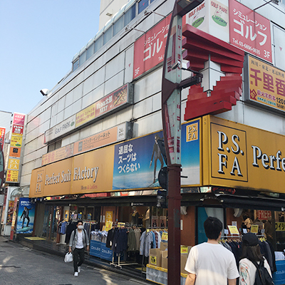 しばらく歩くと、左側に1Fがパーフェクトスーツファクトリーの入ったビル(上野西田ビル)があります。そのビルの5Fになります。エレベーターはビルに向かって左側にあります。