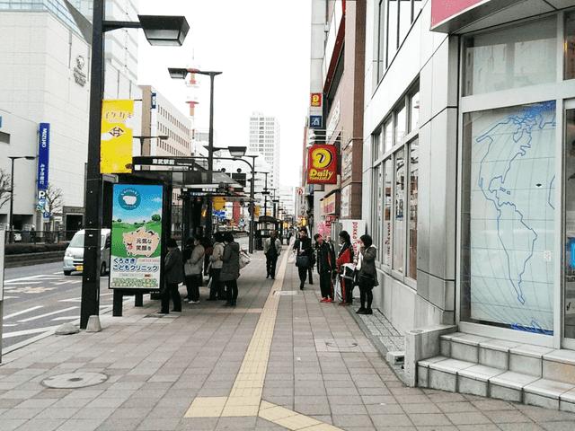 バス停とデイリーヤマザキの看板が見えてきます。