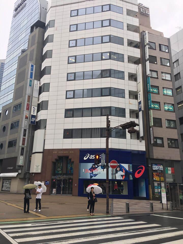 信号を渡ると左手にアシックスが入ったビル、摩耶松本ビルがあります。